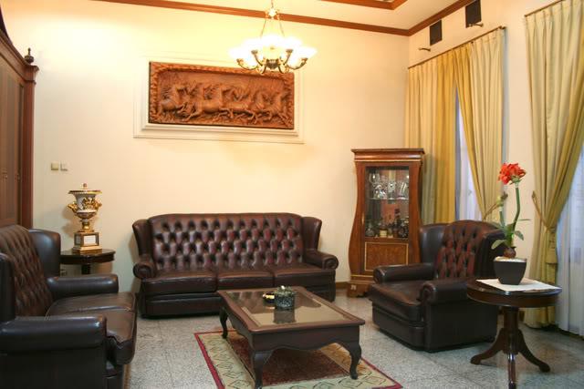 Ruang tamu masa kini dengan sofa coklat serta meja yang elegan